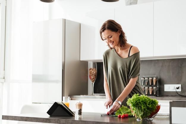 De glimlachende toevallige vrouw snijdt groente door de lijst aangaande keuken en het gebruiken van tabletcomputer