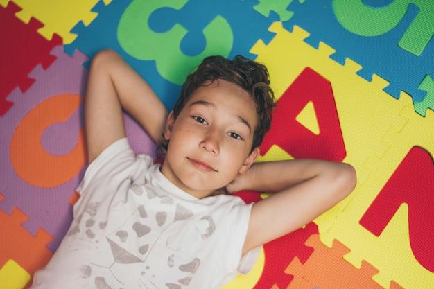 De glimlachende tweenjongen ligt op kleurrijke mat met aantallen en bekijkt camera, mening vanaf bovenkant