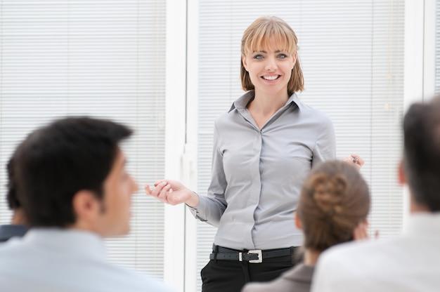 De glimlachende uitvoerende macht bespreekt tijdens een bedrijfspresentatie
