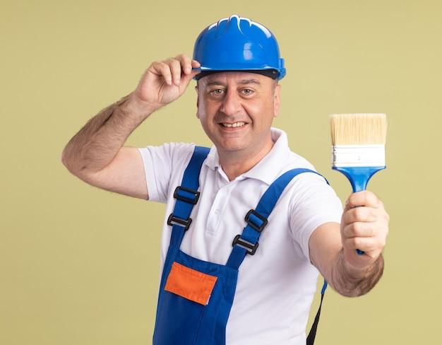 De glimlachende volwassen bouwersmens in uniform houdt verfborstel die op olijfgroene muur wordt geïsoleerd
