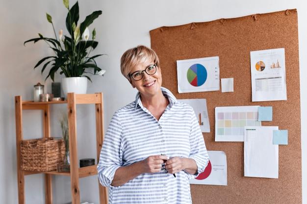 De glimlachende volwassen vrouw in oogglazen stelt in bureau