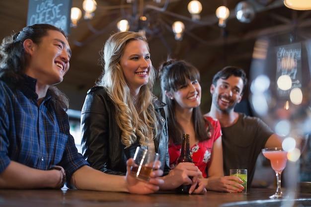 De glimlachende vrienden verzetten zich tegen wegkijken in de pub