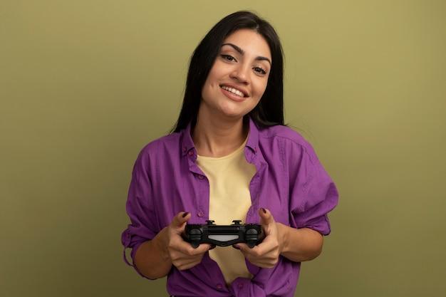 De glimlachende vrij donkerbruine vrouw houdt spelbesturing die op olijfgroene muur wordt geïsoleerd