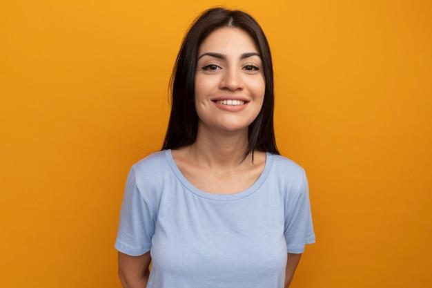 De glimlachende vrij donkerbruine vrouw kijkt naar voorzijde geïsoleerd op oranje muur