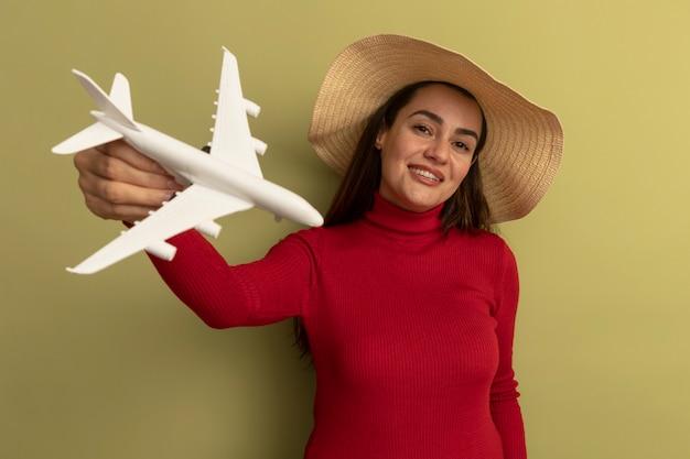 De glimlachende vrij kaukasische vrouw met strandhoed houdt modelvliegtuig op olijfgroen