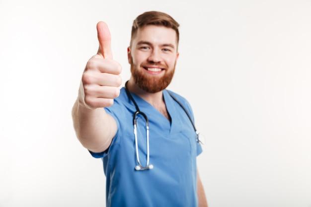 De glimlachende vrolijke mannelijke arts met stethoscoop het tonen beduimelt omhoog