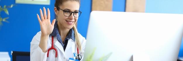De glimlachende vrouw arts heet de patiënt online welkom