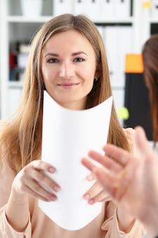 De glimlachende vrouw biedt contractvorm aan