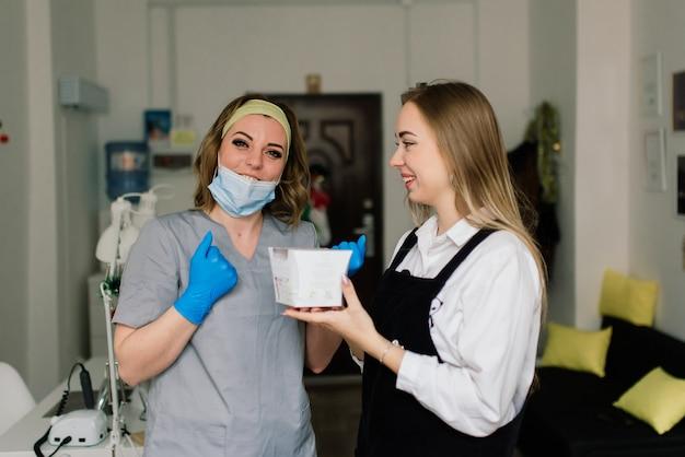 De glimlachende vrouw bij schoonheidssalon heeft een manicure van manicuremeester. meester gebruikt een nagelvijl.