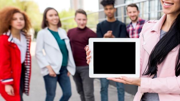 De glimlachende vrouw die lege digitale tablet voor defocused mensen tonen