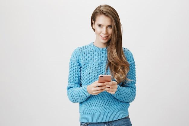 De glimlachende vrouw die mobiele telefoon met behulp van en kijkt camera