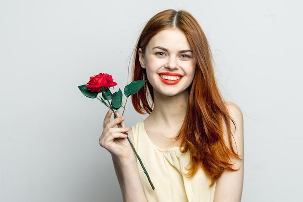 De glimlachende vrouw die roze bloem in handen houdt charmeert rode lippen aantrekkelijk eruitziet geïsoleerd