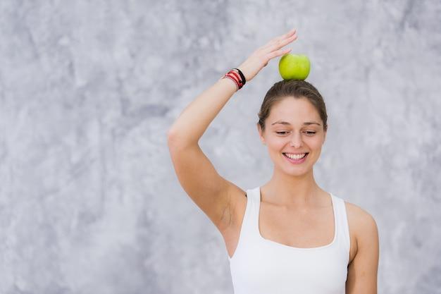 De glimlachende vrouw die yoga doet stelt met appel op haar hoofd