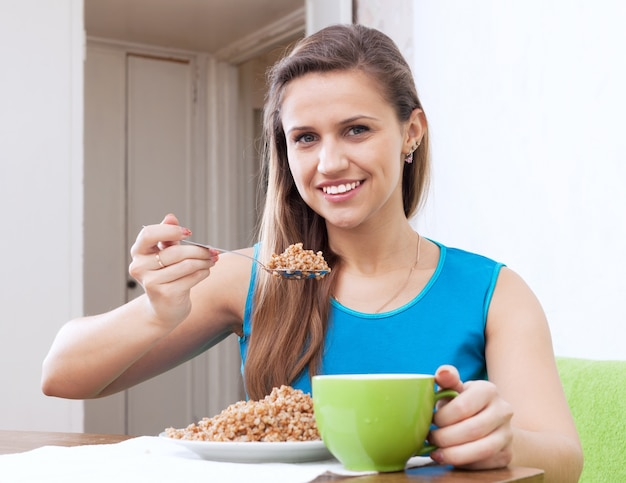 De glimlachende vrouw eet boekweitgraangewas