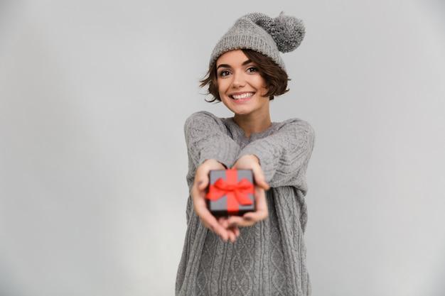 De glimlachende vrouw gekleed in sweater geeft u een gift.