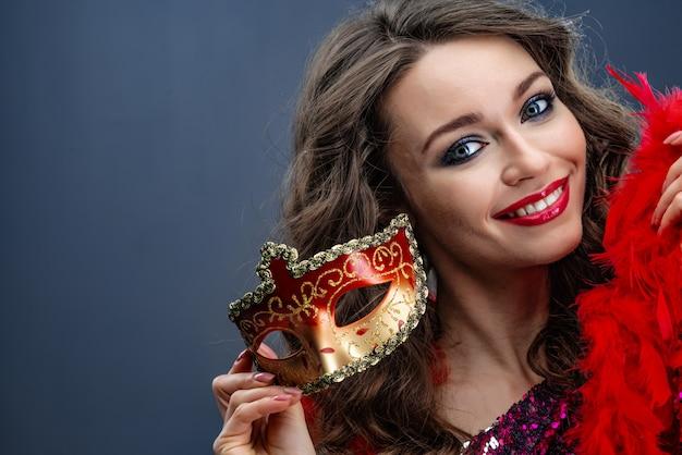 De glimlachende vrouw houdt een boa in één hand in de andere hand met een close-up van het carnaval kleurrijke masker
