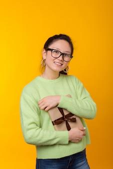 De glimlachende vrouw houdt een verpakt boek als gift