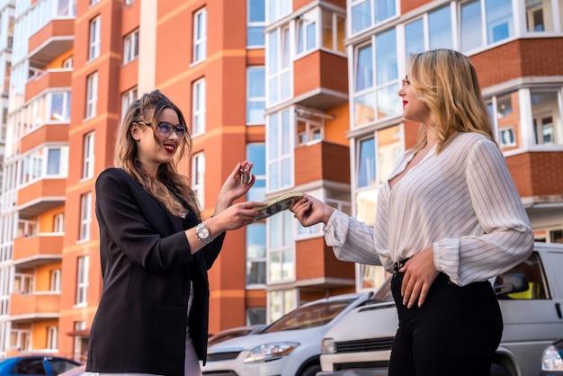 De glimlachende vrouw huurt een nieuw huis en geeft geld aan een makelaar. verkoop concept