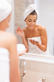 De glimlachende vrouw hydrateert de huid na het douchen