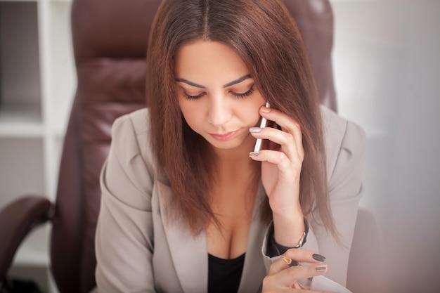 De glimlachende vrouw in bureau spreekt op de telefoon en gebruikt de computerzitting bij de grote desktop