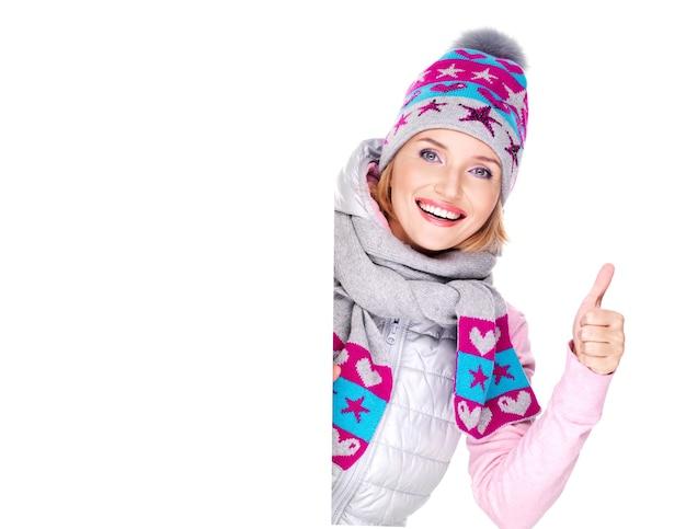 De glimlachende vrouw in de winterbovenkleding houdt het aanplakbiljet met duimen omhoog teken