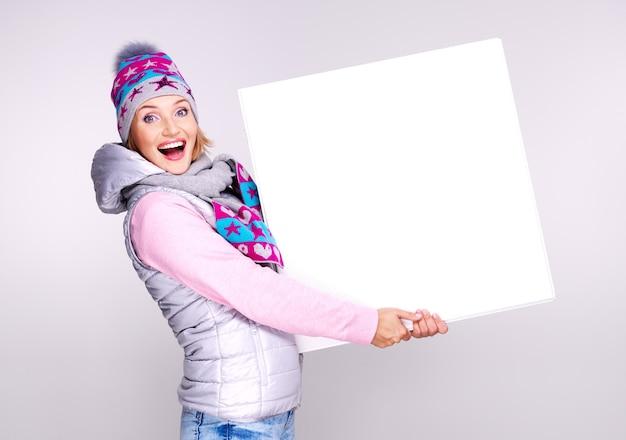 De glimlachende vrouw in de winterbovenkleding houdt het witte bordje in handen