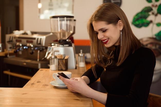 De glimlachende vrouw in een goed humeur geniet van kop van koffiezitting in een koffie.