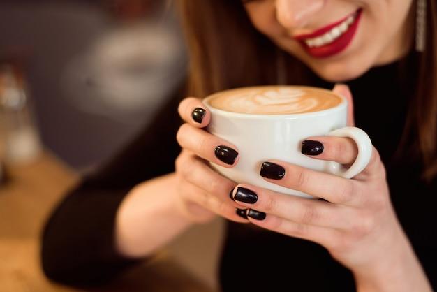 De glimlachende vrouw in een goede stemming geniet van kop van koffiezitting in een koffie.