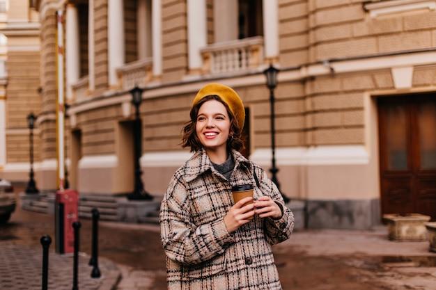 De glimlachende vrouw in gele baret geniet van wandeling door de stad