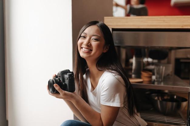 De glimlachende vrouw in het witte t-shirt stellen met voorzijde in haar dient keuken in