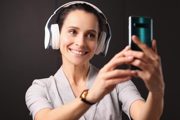 De glimlachende vrouw in hoofdtelefoons onderzoekt smartphone. social media blog introductie concept