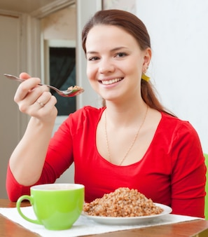 De glimlachende vrouw in rood eet boekweithavermoutpap