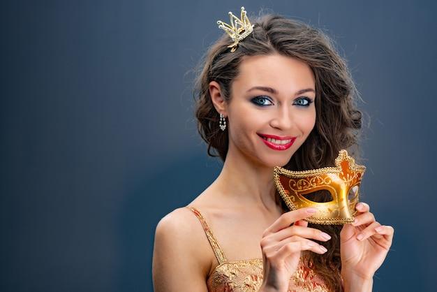 De glimlachende vrouw met een prinses bekroont op haar hoofd en houdt een gouden carnaval-masker in handen