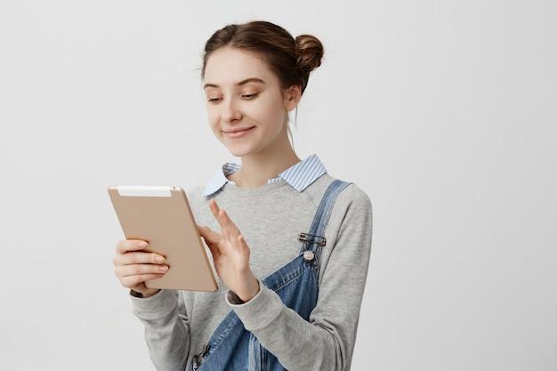 De glimlachende vrouw met haar bond dubbele broodjes vast bekijkend het scherm van modern apparaat. blij vrouwelijke cutie typen bericht aan haar vriend met behulp van tablet. relaties concept