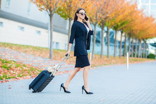 De glimlachende vrouw met koffer en spreekt op telefoon dichtbij luchthaven