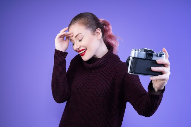 De glimlachende vrouw met rode lippen probeert selfie met een camera te nemen