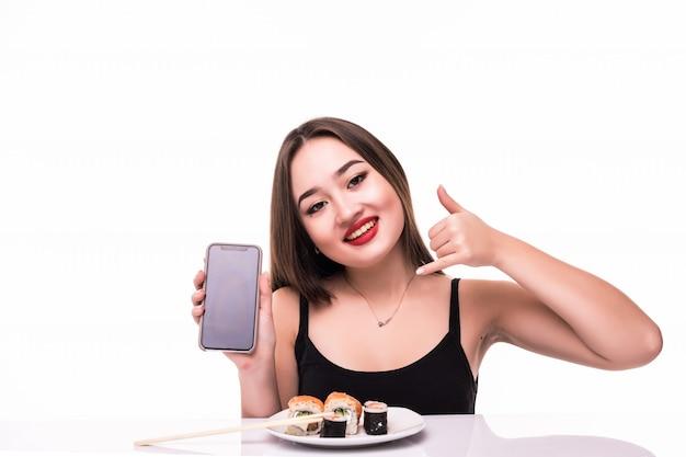 De glimlachende vrouw met zwart haar en rode lippen proeft suushi-broodjes die houten eetstokjes in haar hand houden die op haar telefoon spreken