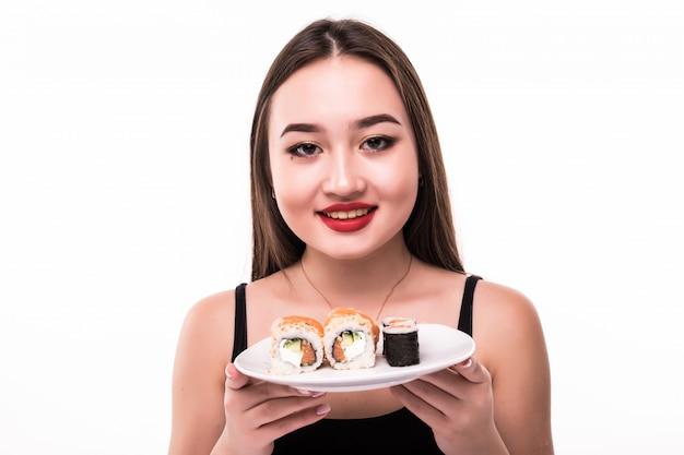 De glimlachende vrouw met zwart haar en rode lippen proeft suushi-broodjes die houten eetstokjes in haar hand houden