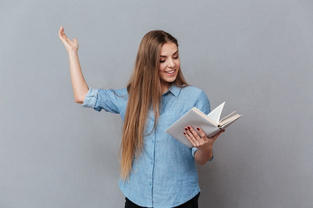 De glimlachende vrouw repeteert met in hand boek
