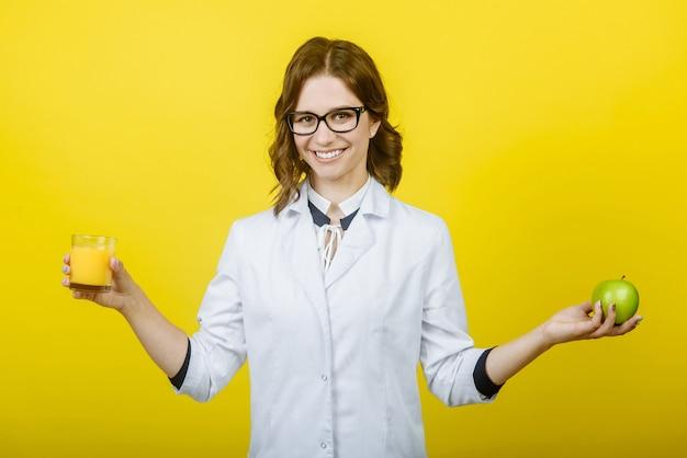 De glimlachende vrouw voedingsdeskundige houdt een glas jus d'orange en een appel, close-up
