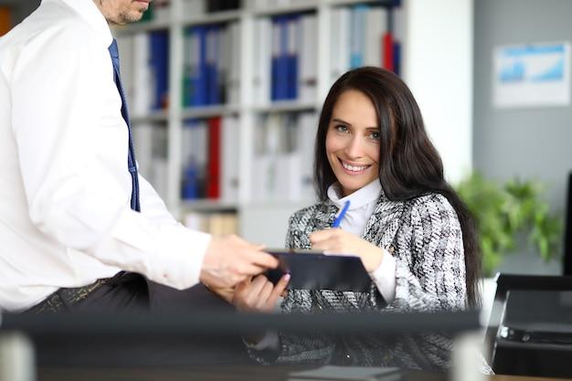 De glimlachende vrouw zet handtekening op documentenclose-up