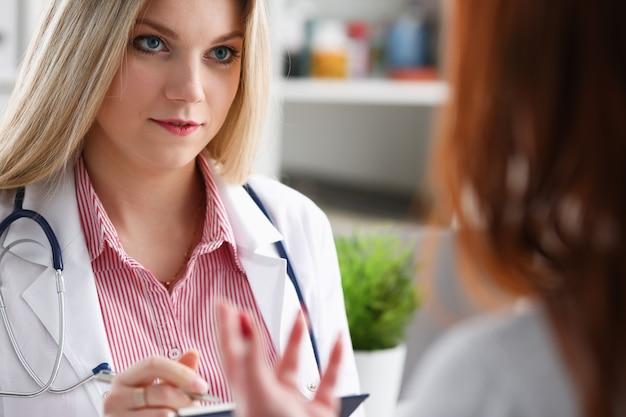 De glimlachende vrouwelijke geneeskunde arts legt uit