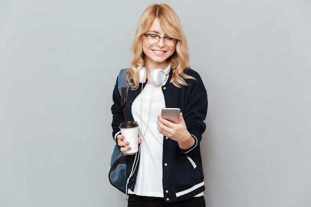De glimlachende vrouwelijke kop van de studentenholding van koffie en het gebruiken van smartphone