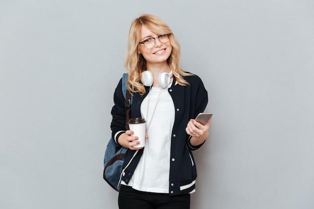 De glimlachende vrouwelijke kop van de studentenholding van koffie en smartphone