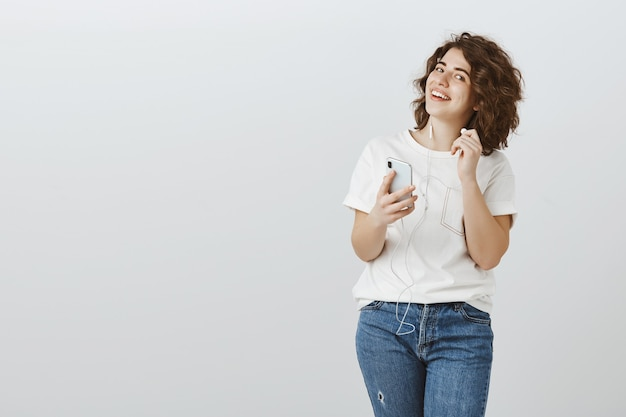 De glimlachende vrouwelijke oortelefoon van de studentenstart en het kijken ondervraagd, luistert muziek