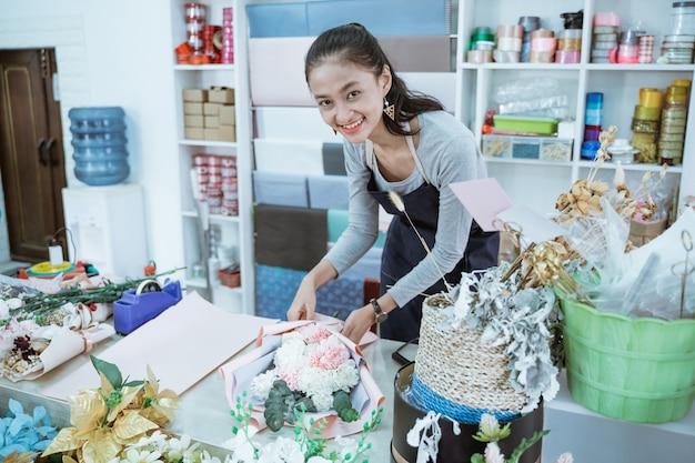 De glimlachende vrouwenbloemist die in bloemenwinkel werkt, maakt orde flanellenbloem in een lijstwerkruimte en bekijkt de camera
