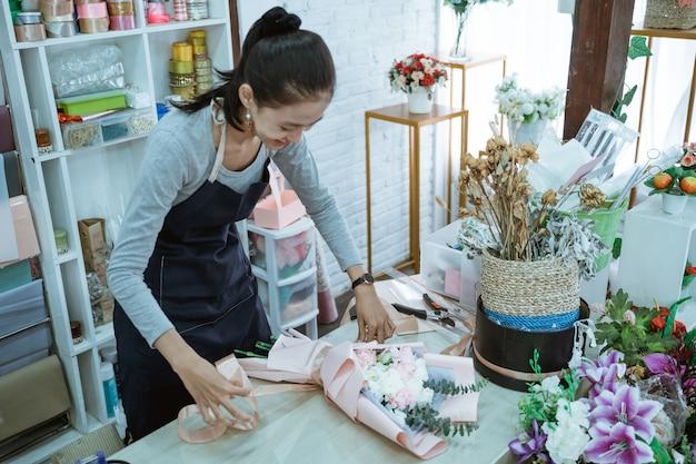 De glimlachende vrouwenbloemist die in bloemenwinkel werkt, maakt ordeflanellenbloem in een lijstwerkruimte