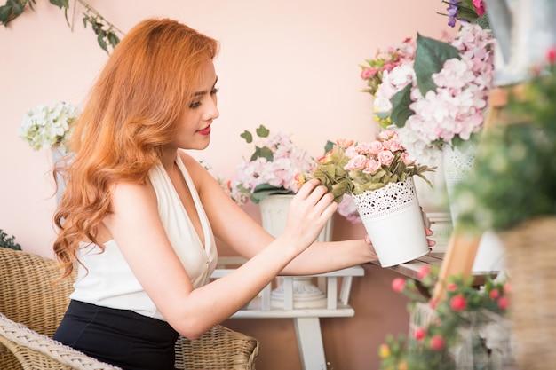 De glimlachende vrouwenbloemist schikt mooie bloemen bij bloemwinkel