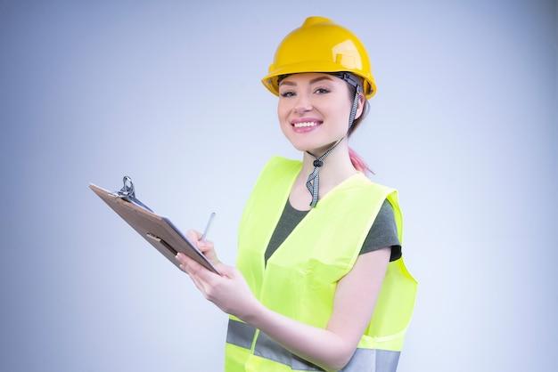 De glimlachende vrouweningenieur in een gele helm schrijft met een pen op een klembord
