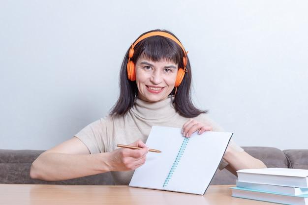 De glimlachende vrouwenleraar in hoofdtelefoons legt de les uit door op een leeg oefenboek te tonen